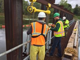 DNR official providing contractors with assistance in removing stop logs from temporary water control structure to lower water level in work area