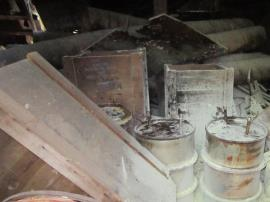 5 metallic potassium vessels were located in a barn at the site.  Three of the metal containers are visible picture-center.  Two metal containers were within wooden shipping crates (center-back).