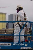 PAC/PAS asbestos technician is suited up in Level C with fall protection, preparing to lift up to the top of a filled truck to staple the liner closed. Photo taken from River Street.