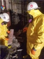 Crew members spray water on insulation bricks that contain friable asbestos to reduce the dispersion of the particles during removal.