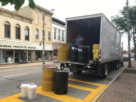 Chemtron loading labeled packed containers into semi-truck for off-site disposal.