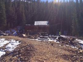 View of cabin on site taken from the top of the waste rock pile before work began. Photo was taken facing toward the collapsed adit.<br />Date Taken: 10/10/2017<br />Category: Site Photo<br />Latitude: 39.5981757<br />Longitude: -105.8534054<br />Tags: Original Conditions