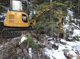 Excavator working in trees constructing channel below adit next to cabin on top of waste rock pile.<br />Date Taken: 10/11/2017<br />Category: Site Photo<br />Latitude: 39.5980383<br />Longitude: -105.8534389<br />Tags: Construction Activities