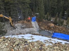 Limestone being placed into Channel liner at lower edge of waste rock pile. Looking down from waste rock pile.<br />Date Taken: 10/16/2017<br />Category: Site Photo<br />Latitude: 39.5983648<br />Longitude: -105.8539271<br />Tags: Construction Activities