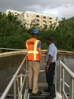 EPA personnel survey a settling tank at a wastewater treatment plant.
