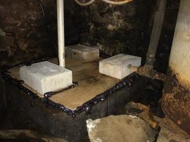 Northern sump with sealed cover in place. The plywood was included as a cover over 3/8-inch thick, fitted acrylic sheet to provide added structural stability. The concrete blocks were included to provide temporary pressure while the foam sealant installed at all gaps set.<br />Date Taken: 9/20/2018<br />Category: Site Photo<br />Latitude: <br />Longitude: <br />Tags: