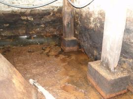 Basement, facing approximately west, showing spring entrance location (behind post in center of photograph) and non-air tight rubber matting covering the channel between the spring and south sump. At the time of the photograph (June 2013), the floor had been recently cleaned of sediment and was damp.<br />Date Taken: 6/25/2013<br />Category: Site Photo<br />Latitude: 40.544241<br />Longitude: 75.12875<br />Tags: