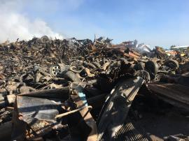 Partial view of burned scrap metal piles on Site.