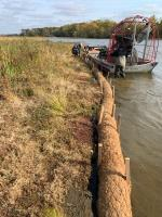 Coir logs being installed along banks in upstream of the dam susceptible to erosion during high water events