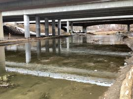 Southwestern facing view of previously collected surface water sample location LDS-05 at underpass of I-25. No sheen visible in the area.