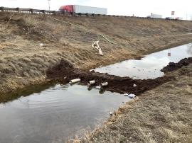 Eastern facing view of underflow dam 1, located along drainage ditch west of I-25.  Feature is holding back apparent heavily impacted material to the south and discharging apparent clear effluent to the north. Light sheen visible to the north of feature