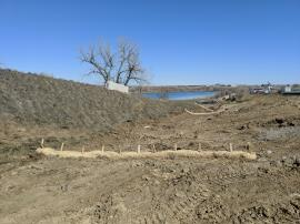 Straw wattles installed across the drainage ditch west of I-25 South.