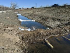 Underflow dam contructed across drainage ditch west of I-25 South. Absorbent boom placed across drainage ditch upstream of dam.