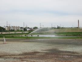 Contractors set up the sprinklers to water the hydroseeded areas.