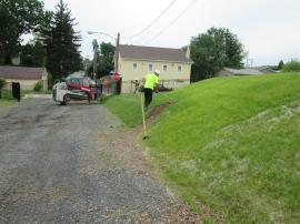 Contractors mow the entrance berms and fill in the bare areas with topsoil. The bare areas were caused by the erosion control socks.