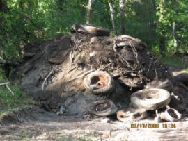 Construction debris (metal sheeting and piping, asphalt, brick, concrete, etc.) and tires excavated from one of the test pits.