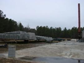 Southwest corner of facility/building with isolated drum on pad and tub/spa curing stands to the left.
