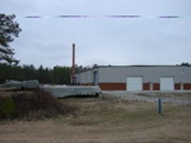 View to the north of the west side of the facility.  Spa/pool curing stands and exhaust stack.