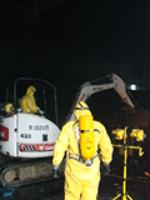 RP Cpntractors working inside the building to clear fire-damaged or fallen debris to access chemical containers.