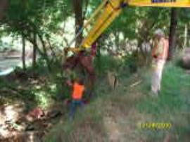 Track hoe being utilized to retrieve drums in Johns Creek