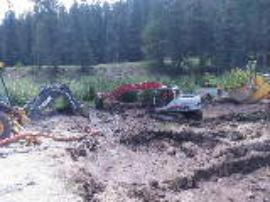 Removal of material following dewatering of containment pond.
