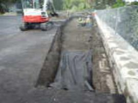 Asphalt repair and first layer of backfill, placed in lifts.