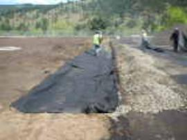 Placement of geotextile fabric along drain rock apron.