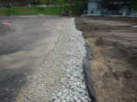 Final drain rock apron along interface of asphalt and dry retention basin.