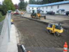 Compacting 6-inch lifts in asphalt repair area.