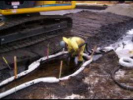Workers use vacuum hoses to pull sheen out of the recovery trench.