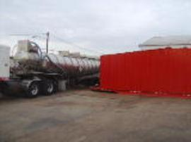 Hazardous waste liquid pumped from frac-tank into tanker truck for transport off site
