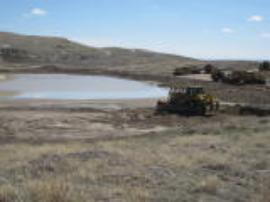 Bulldozer pushing tailings back into the pond (old mine pit).<br />Date Taken: 5/1/2013<br />Category: Site Photo<br />Latitude: <br />Longitude: <br />Tags: