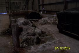 Piles of unknown solid material between roll-offs with similar material in warehouse.
