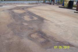 Stain on concrete where waste oil had leaked from frac tank.  Note floor drain in upper center right where leak flowed overland.