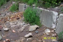 Brown leachate from contaminated soil pile (left of center) coming through gaps between Jersey barriers.