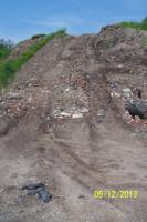 View of roadway cut into large soil pile by ERRS to gain access to top of pile to lay tarps.