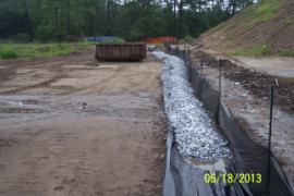 Second rainwater diversion trench running West to East between soil piles and retention ponds.