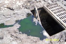 View of leachate from contaminated soil piles  running into sump for collection.  Note greyish soild sediment around opening.