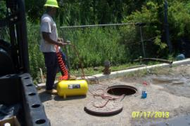 ERRS tech using compressed air to inflate rubber pig (inside manhole) to block storm drain line that feeds into the retention ponds.