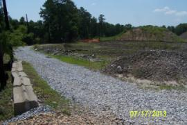 Newly installed crushed stone on roadway around retention ponds (on right).  Stone provides a stable/dry base for access and increased the free-board in the ponds by 2 inches.