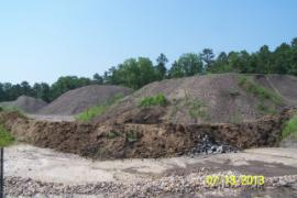 Rock and earthen berm constructed between contaminated soil piles to contain silt.
