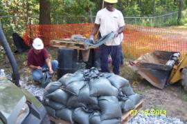 Crew filling sandbags used to weigh down poly sheeting strung over rock wall separating the two retention ponds.