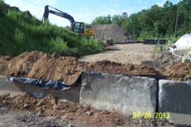 Bermed and lined barrier between two soil piles where thickened sediment will be staged.