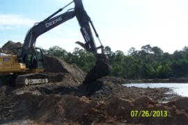Excavator mixing soil with dredged sediment to absorb water and reduce runoff.