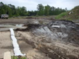 View of contaminated sludge scraped from roadway, looking towards retention ponds, soil piles on right.