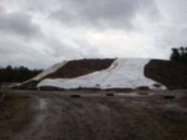 View of large soil pile after storm, tarps partially disrupted.