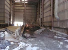 Interior of Bldg. #3 showing mixing pit full of waste.  Flat area to left has been cleaned.