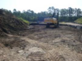 Area for dredge spoils being prepared.  Dirt from this excavation was used to create a barrier between dirt piles to prevent migration of contaminated silt.