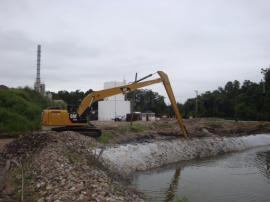 Long reach excavator dredging retention ponds.