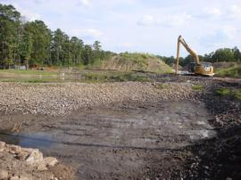 Final view of portion of retention pond after sediment removal, rock washing and repositioning of rocks to smooth bottom of pond.